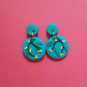 Australian Flowering Wattle Earrings Handmade with polymer clay on a blue background